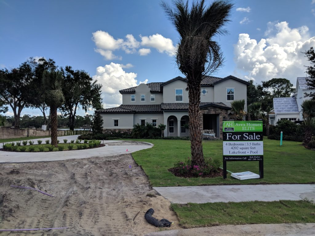 Complete view of new home including driveway, landscaped front yard area and views of Lake Mary in Central Florida.