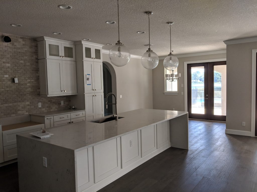 View of kitchen area including island feature, cabinets, dropped lighting fixtures, countertop, and wood flooring with double doors leading out to backyard.