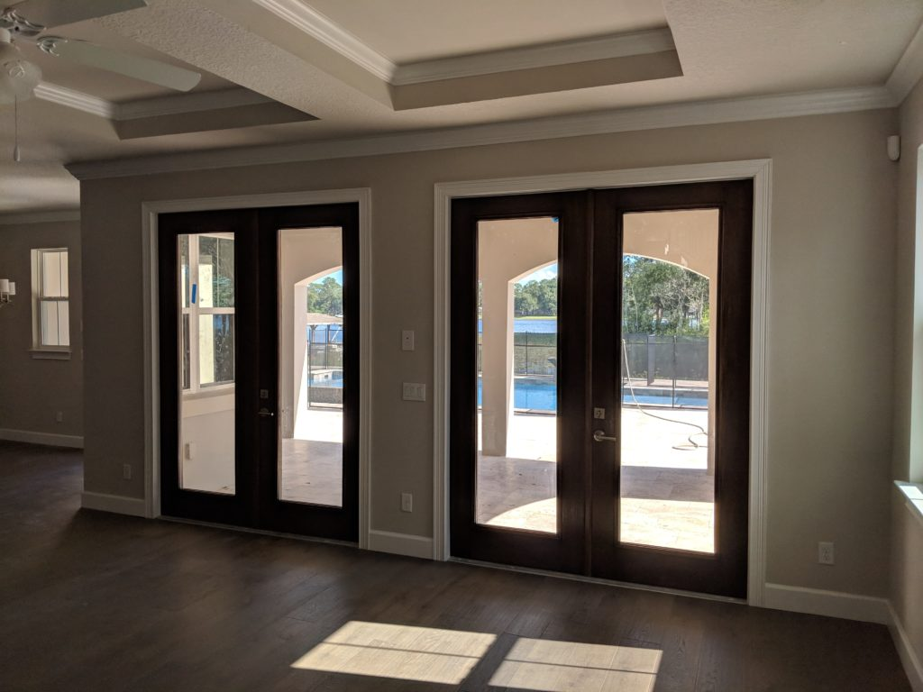 Room with coffered ceilings and double doors with large glass inserts look out to backyard with gated pool and lake view.