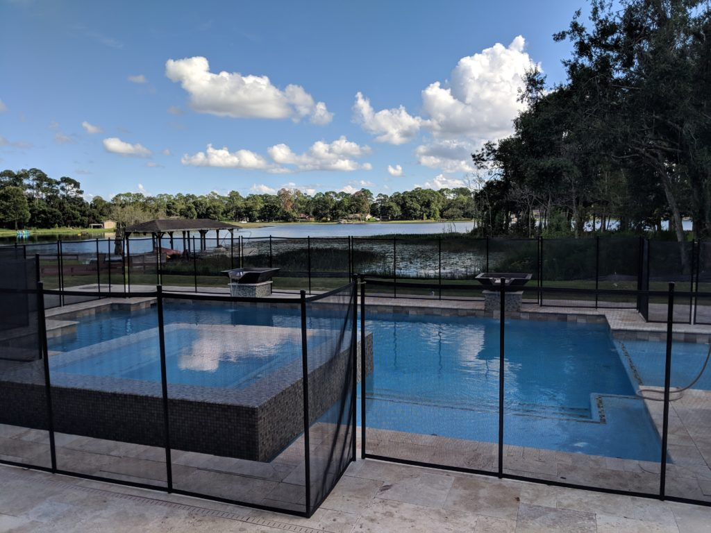 Waterfront pool with sundeck sits in the backyard with safety gate around pool structure and paved area.