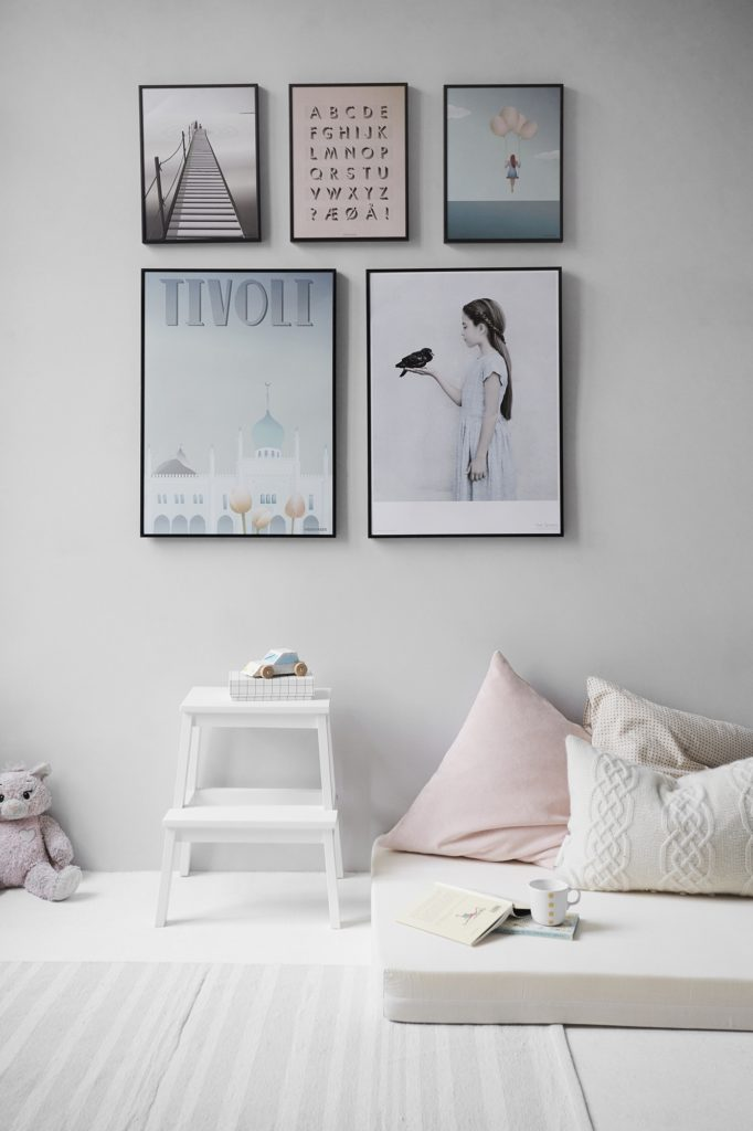 Pictures hung on a wall of a new home with pillows in the ground and light pastel colors themed for a child.