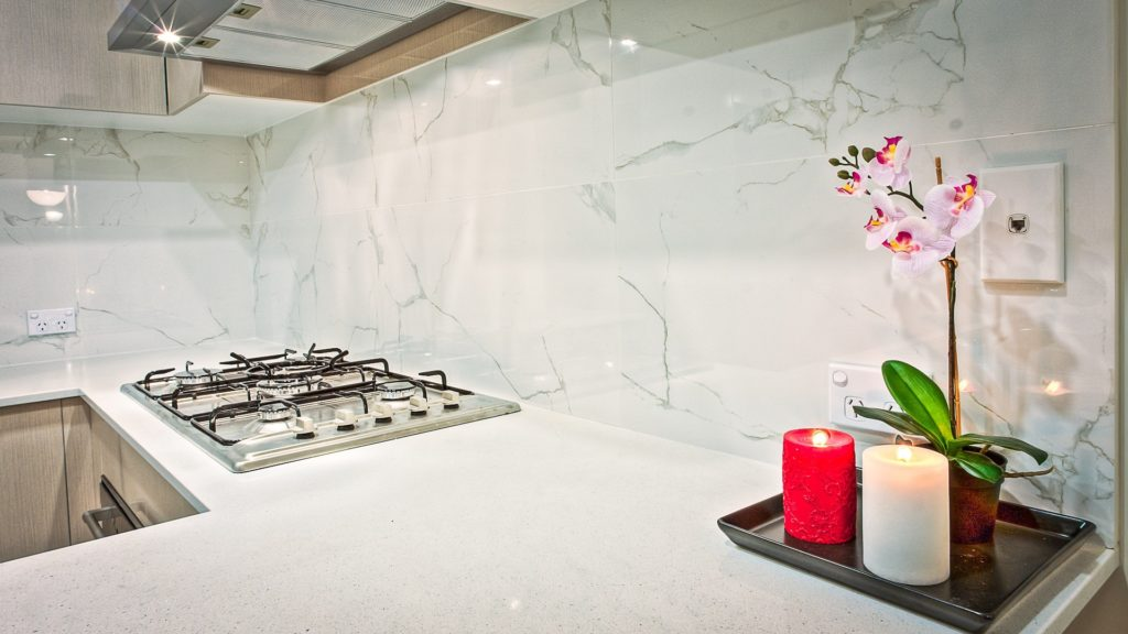 Crisp white theme in a sample kitchen with candle and flower detail on countertop in a new home.