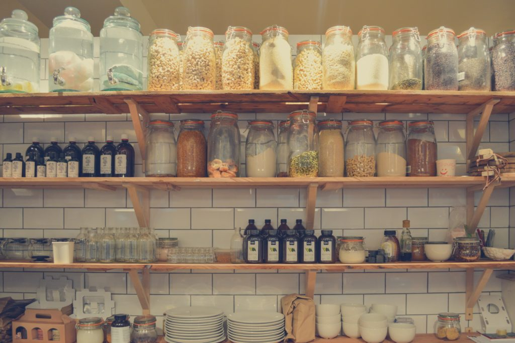 Storage containers, jars, labeled containers and more on wooden shelves in a pantry with tile wall feature.