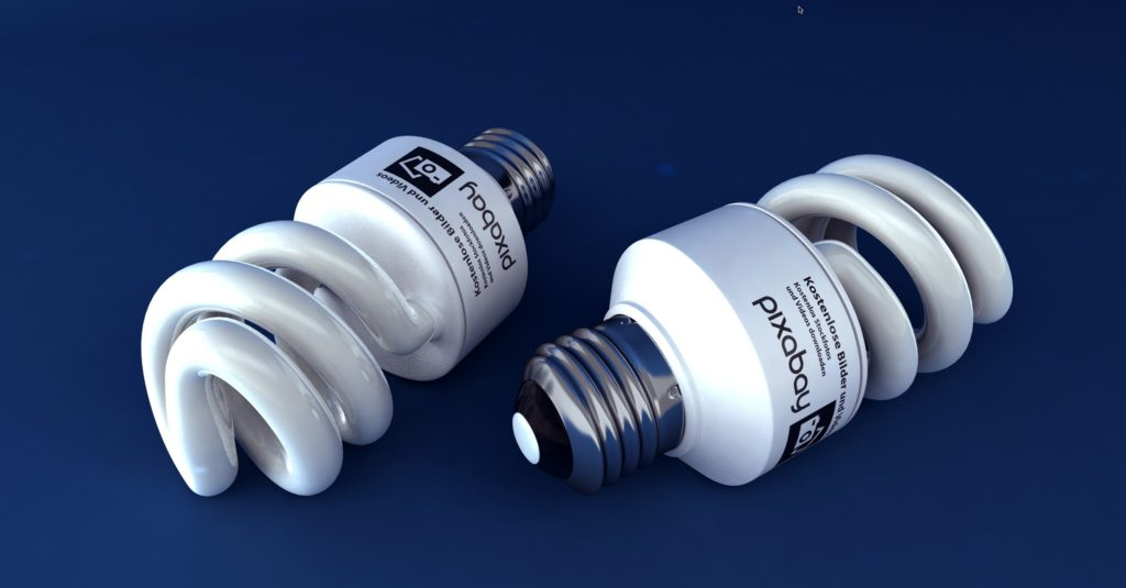 Two energy efficient light bulbs lying down in opposite directions to show all features of the bulbs.
