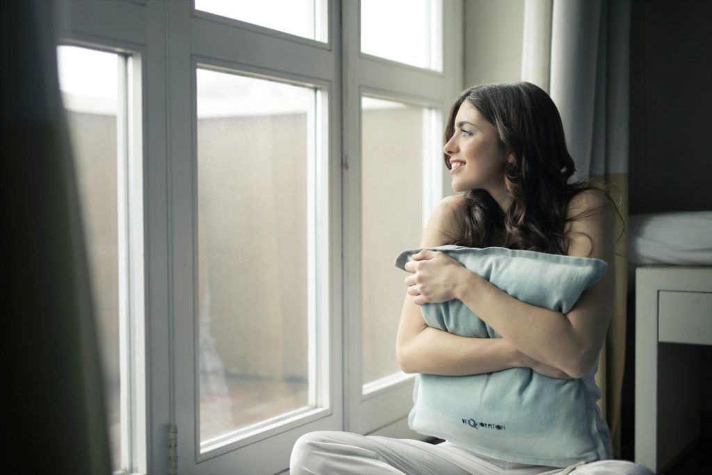 Woman holding a pillow in a new home looking out of energy efficient windows that help insulate the air in and keep out the outside air.