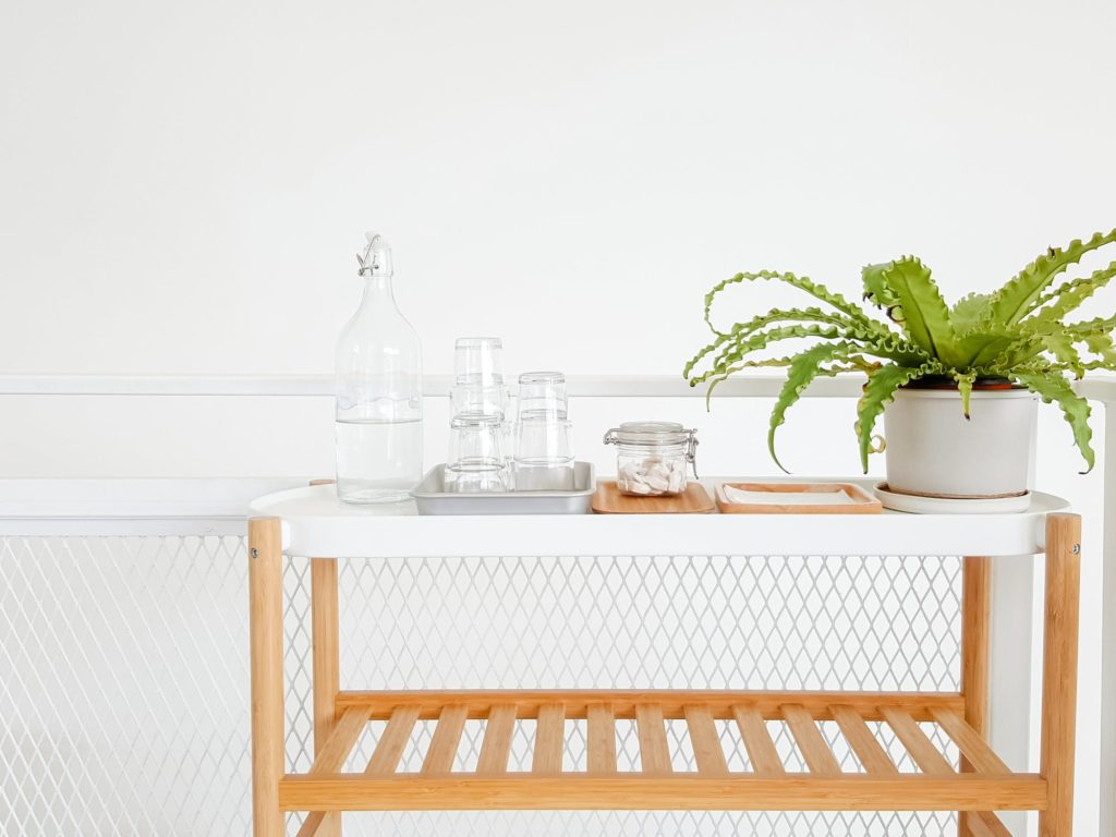 Clean all white bathroom with plant and glasses atop a wooden table in a new home.